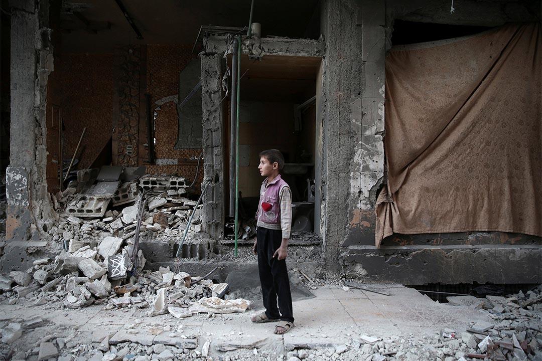 2016年10月4日,叙利亞大馬士革遭空襲後,一個男孩站在損毀的樓房前。