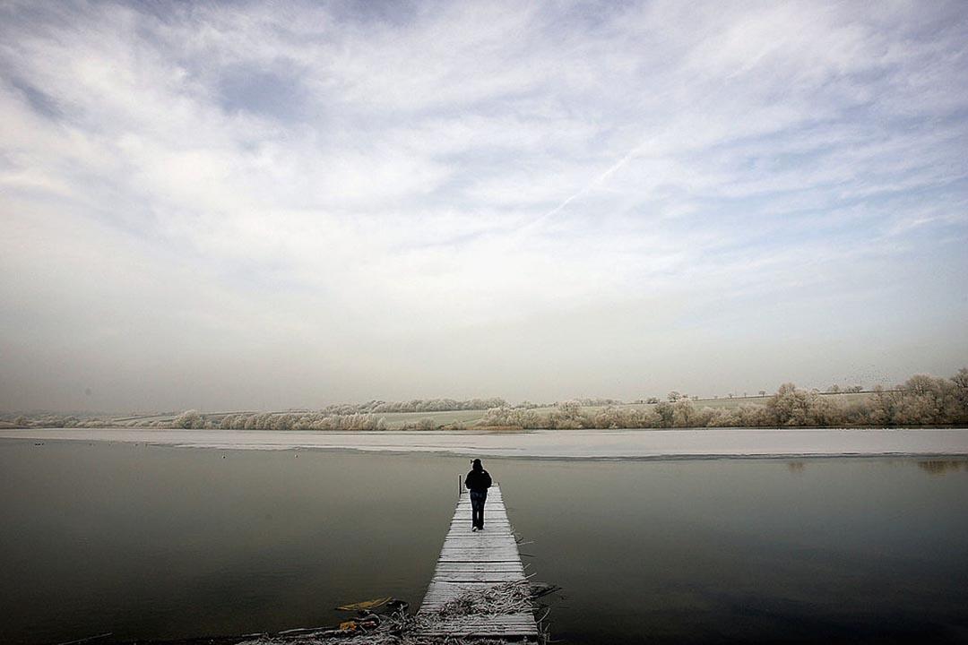 圖為英國一個人走近結霜的湖面。