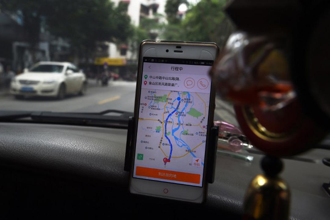 一名出租車司機在車上使用網約應用程式。