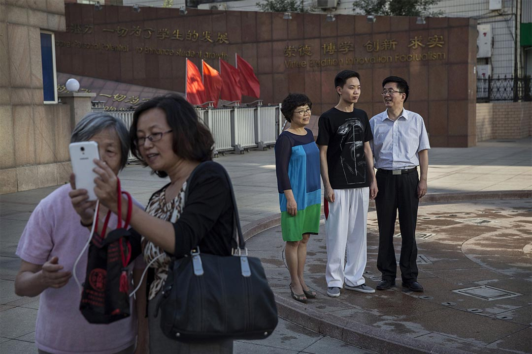 圖為2015年6月8日,中國北京,一個學生在校門外與家長合照。