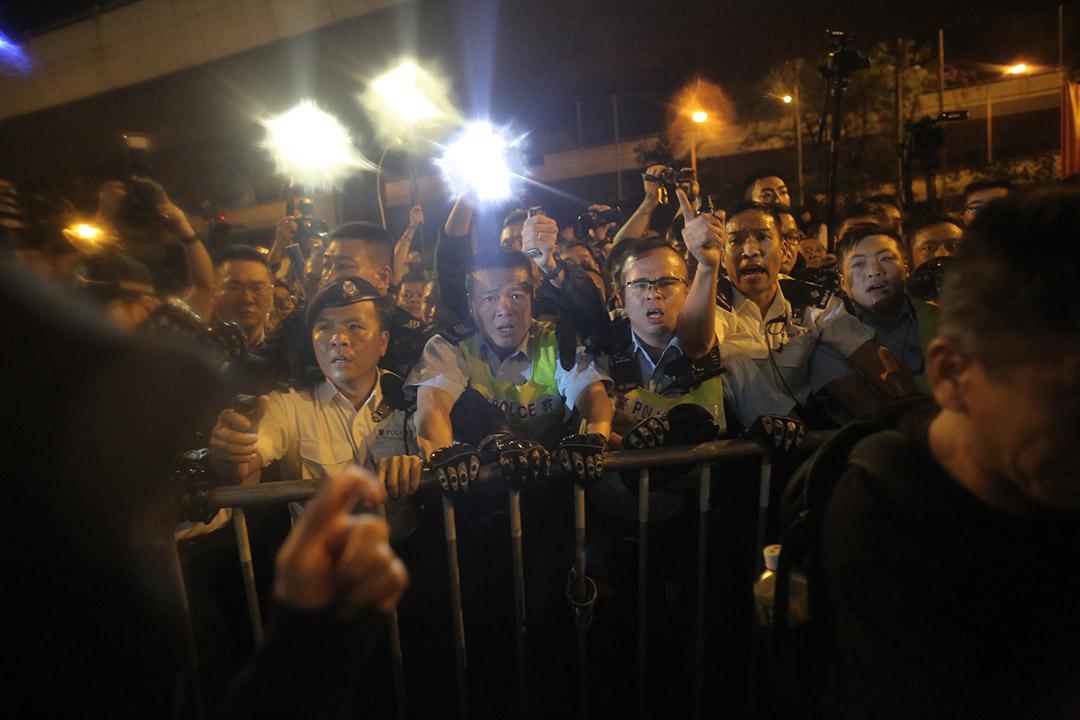 晚上近8点,在中联办外聚集的示威者冲出并与警发生冲突。