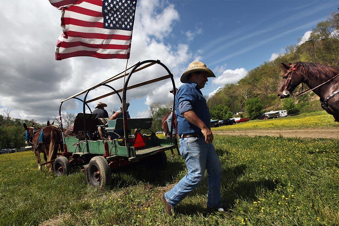 2012年4月20日,美國布恩維爾奧斯利縣,一個男人走在馬車旁。