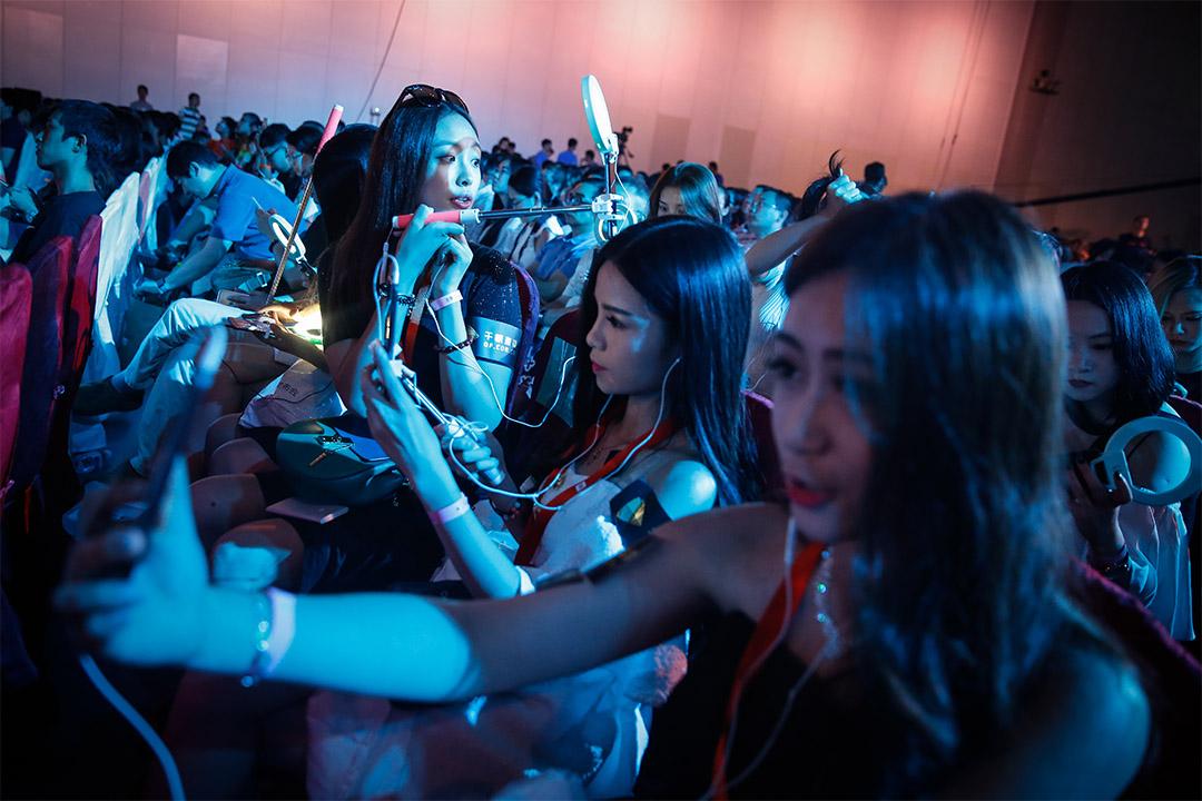 圖為一群網絡主播手持手機在產品發布會上現場直播。
