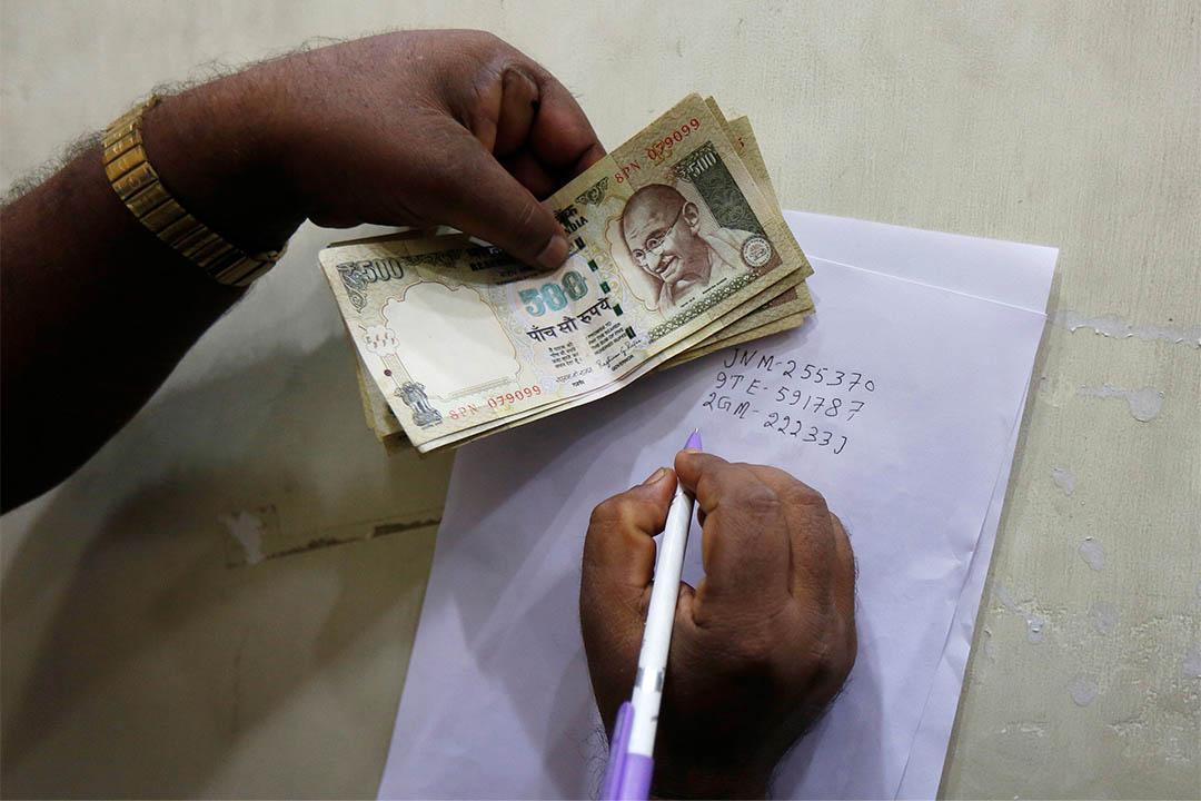 2016年11月13日,印度加爾各答,一個人在將盧比存入銀行前,抄下鈔票的序號。