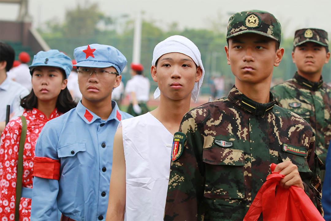 新華社批學校全員入團現象。圖為2016年9月11日,江蘇南通市一所中學內,高中學生進行軍訓彙報展演。
