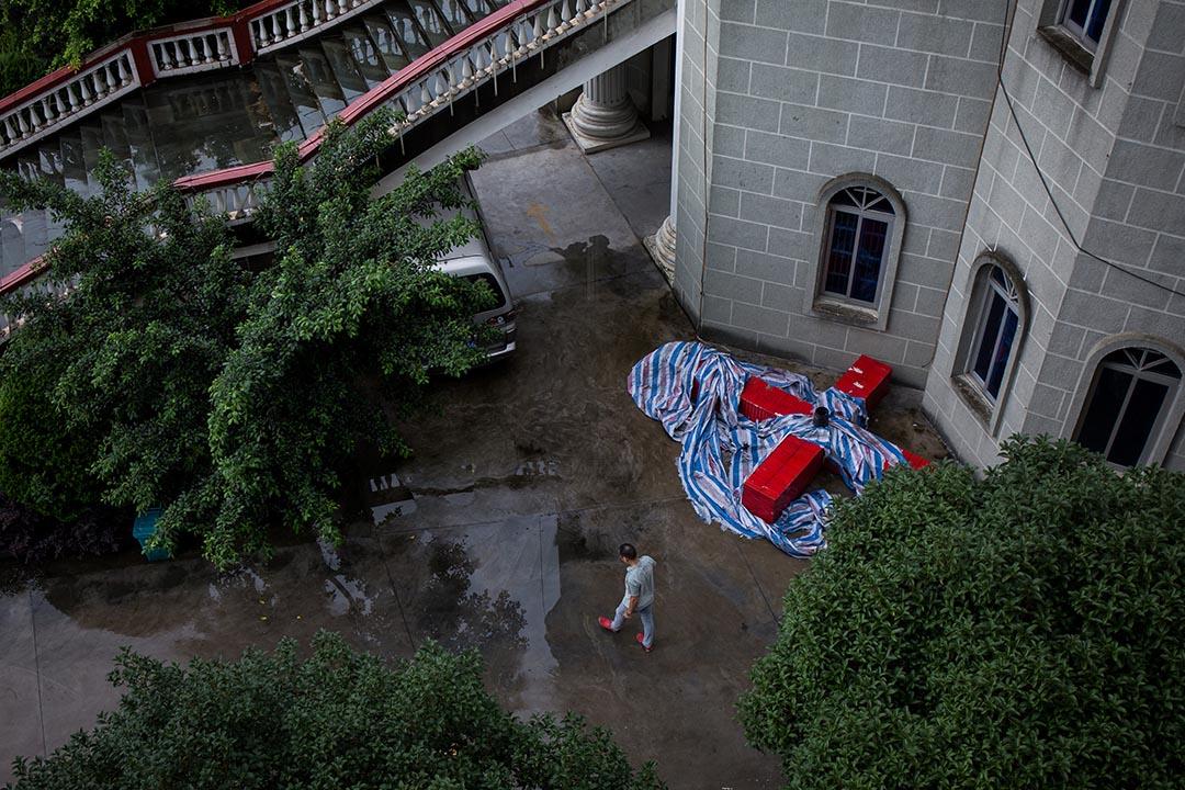 温州一家教堂外,市民在一目被拆下的十字架前走过。
