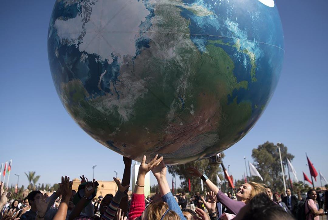 各國國際代表團成員在COP22場外玩一個巨大的地球模型。