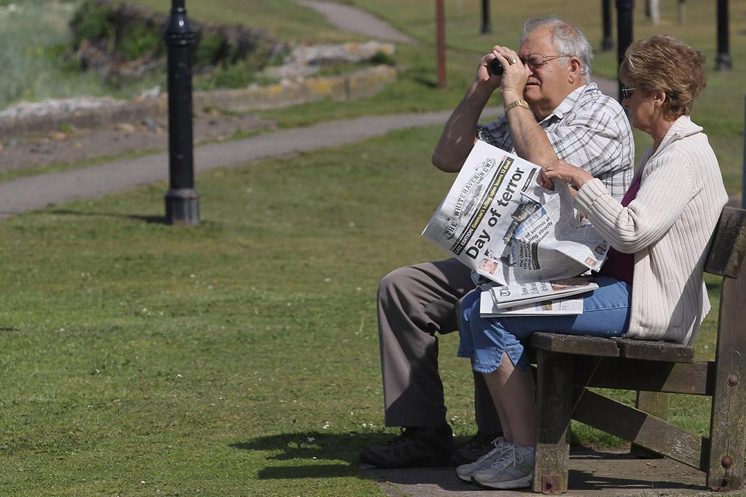 老人在公園看報紙。