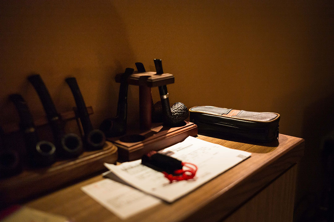 他的家裏裝潢也簡簡單單,收藏幾根菸斗,一櫃書,一些國徽紀念品。