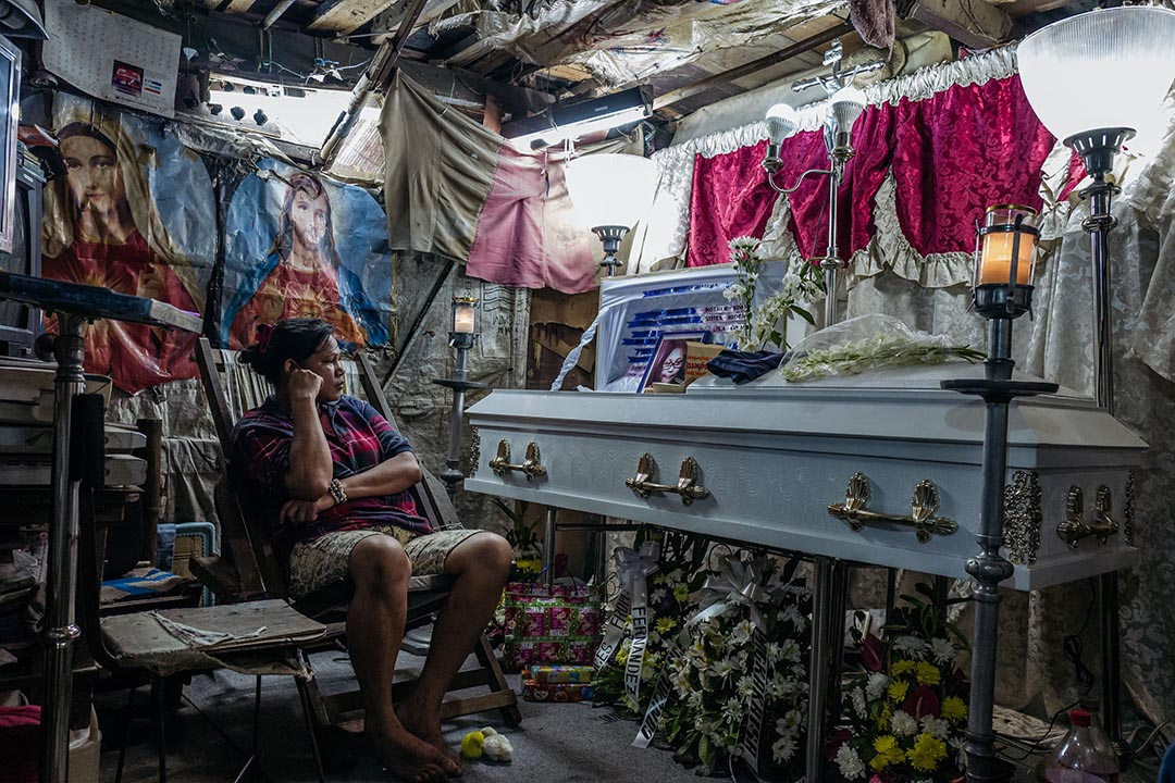 平安夜當晚,在小城比尼安(Binan)一條小村落,Kimberly Sailog守在孻女的靈柩旁。設靈期間放置小雞是菲律賓中部與南部的殮葬傳統,當地人相信會為枉死之人帶來公義。