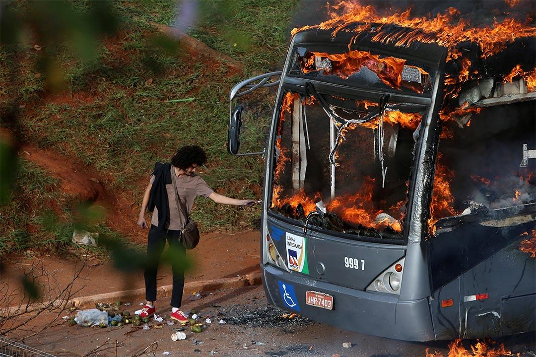2016年12月13日,巴西,群眾在反政府示威中焚燒一輛公共汽車,一個人用火焰來燃點香煙。