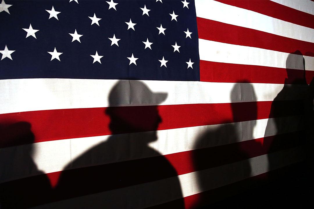 2016年2月11日,幾個人站在美國國旗後面。