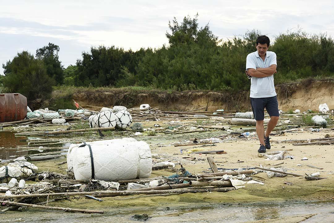 洪篤欽沿着海岸步行,習慣隨手翻翻垃圾,檢視來源。