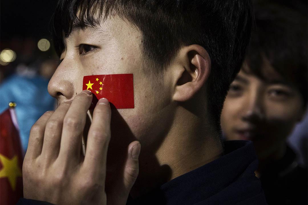 2015年10月1日,中國北京天安門國慶升旗禮中,一個青年摸著面頰上的國旗圖案。