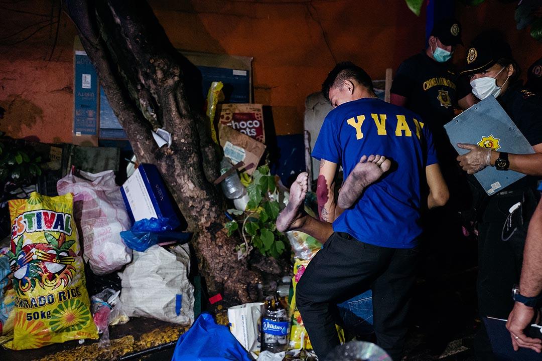 在其中一個位於貧民區的「反毒行動」現場,鑑證人員正抬出一具屍體。