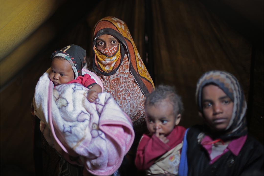 2016年2月,也門阿姆蘭(Amran, Yemen),一個婦人與她的孩子們在市郊一個營地裡棲身。該營地接收了為逃避沙特聯軍與胡塞武裝部隊戰鬥,而被迫離開家園的人。