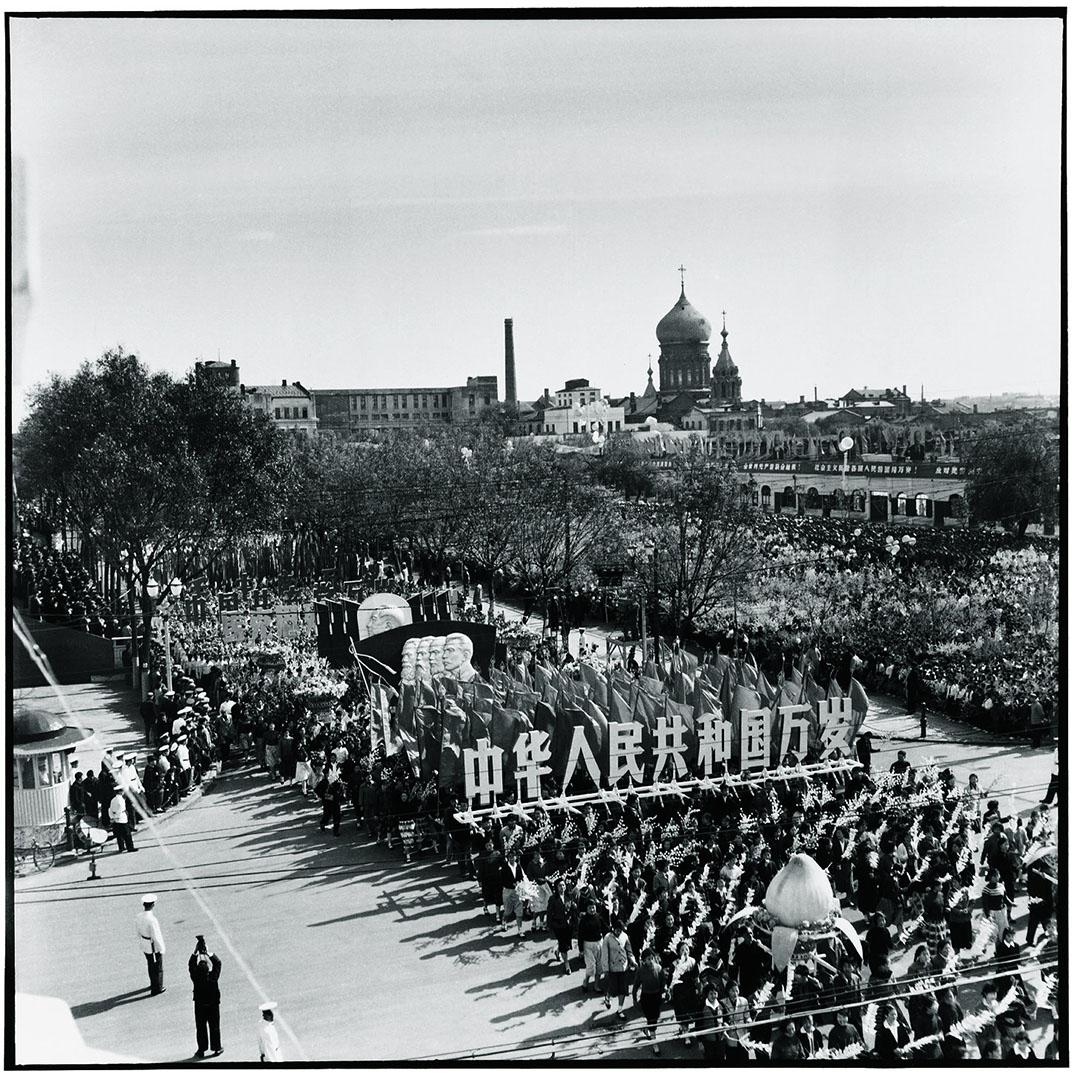 1963年10月1日哈爾濱,國慶閱兵期遊行人士高舉寫着「中國人民共和國萬歲」大字的木板,其後是毛澤東、馬克思、恩格斯、列寧、史達林的頭像。旁邊是聖索菲亞大教堂。