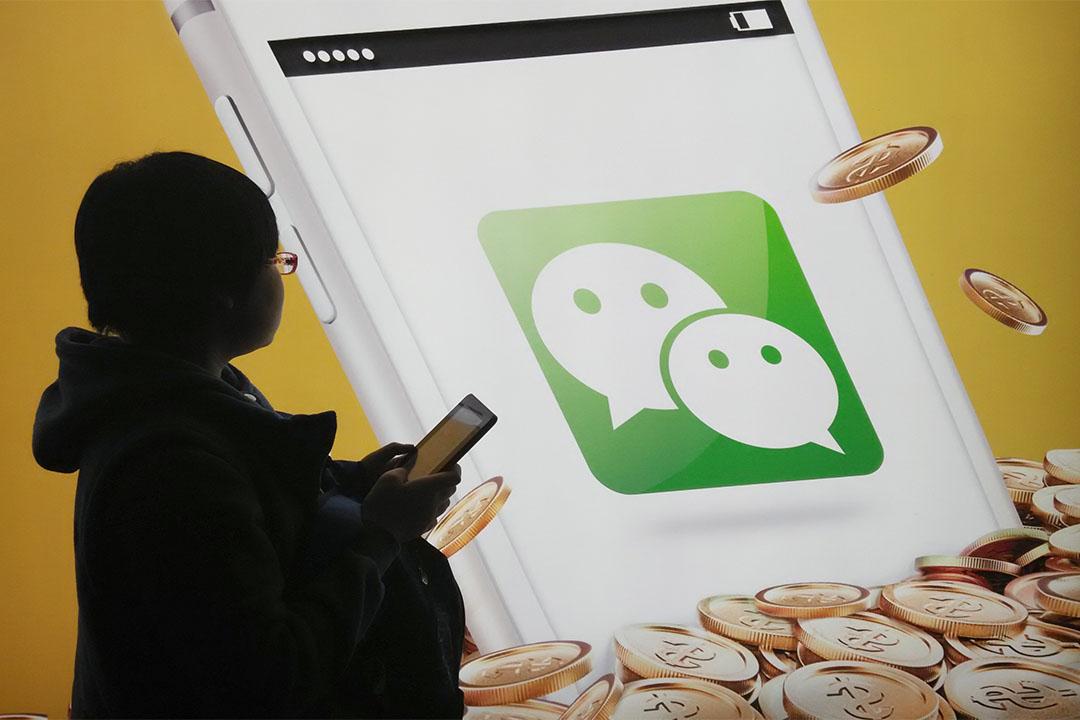 2015年2月16日,中國北京,一個行人走過微信標誌。