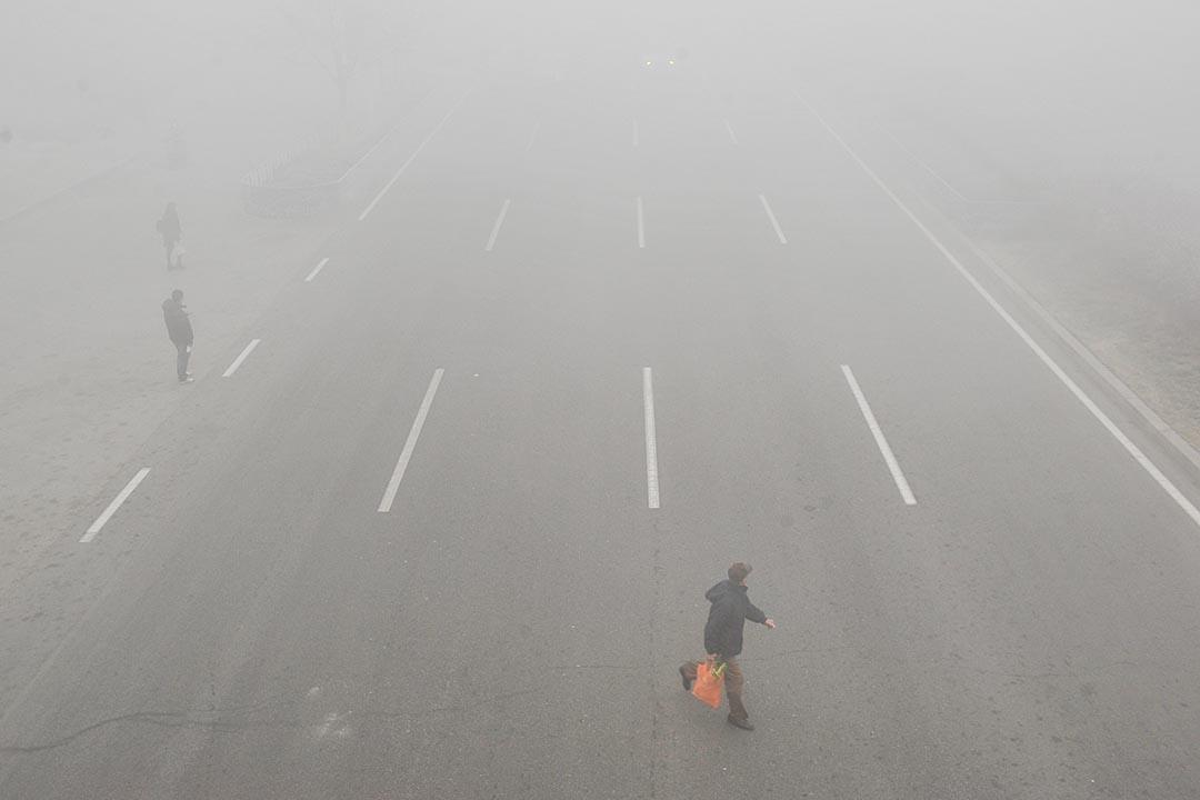 中國天津,市民在霧霾中橫過馬路。