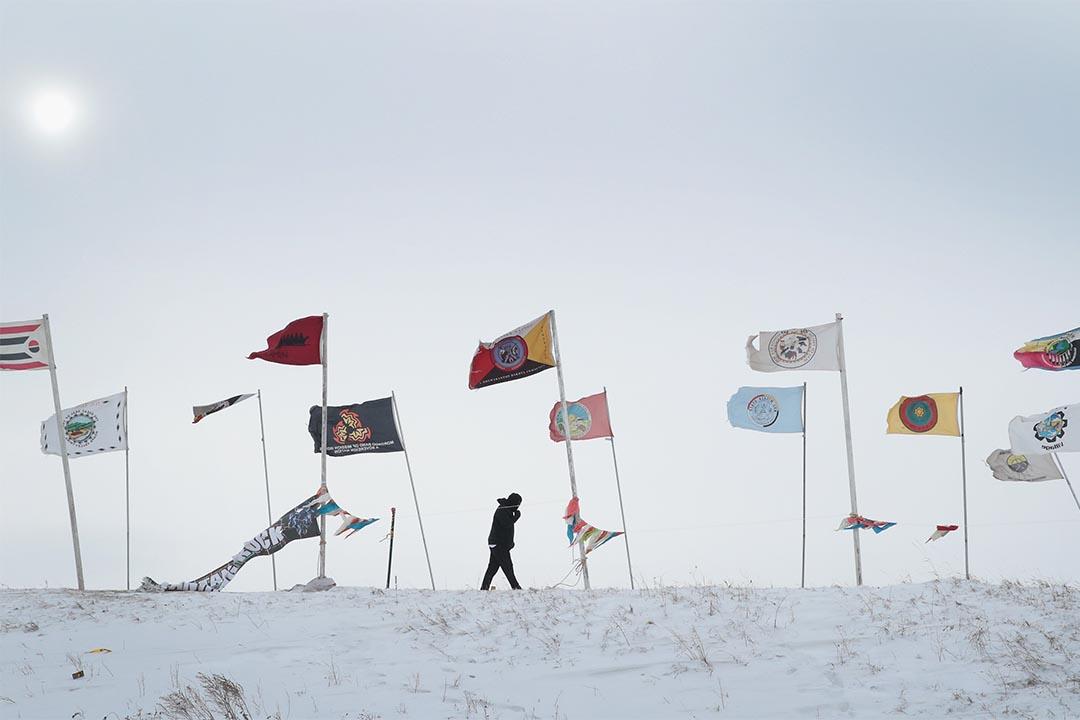 2016年12月6日,北達科他州反對興建輸油管的抗議繼續,一個示威者在寒風中走過營地。