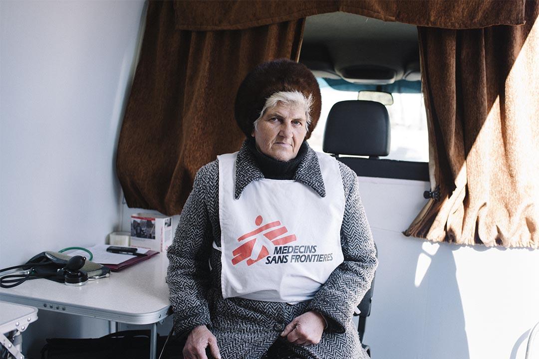 2016年3月,烏克蘭馬約斯基(Mayorsk, Ukraine),一名無國界醫生志願健康工作者坐在以小型貨車改裝而成的流動診所的後座。這間流動診所專為接近烏克蘭政府軍與反對派衝突前線的馬約斯基的居民提供服務。