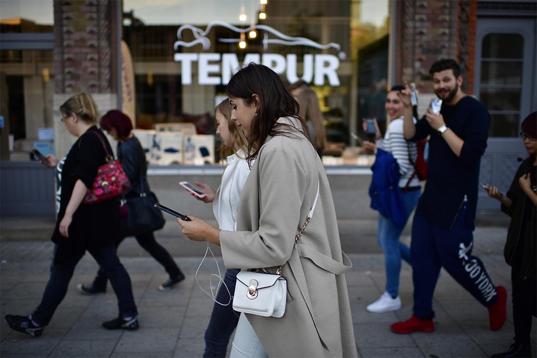 從 Facebook 脫身可以提升情緒與生活滿意度,重度使用者尤其明顯。圖為德國街道上,人們看著手提電話。