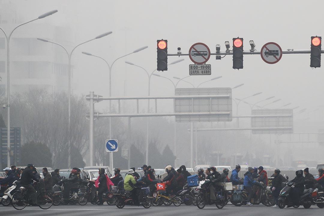 中國北京,市民騎單車和電動車橫過馬路。