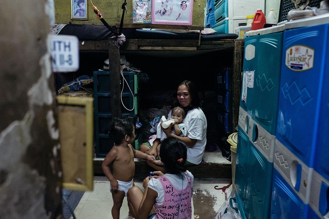 Gina De Lemon 一家八口棲居於馬尼拉三巴樂市(Sampaloc)貧民區一所由木板、鐵皮與尼龍膠袋搭建而成兩層高的寮屋上層。