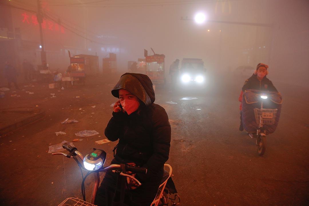 中國河北,市民騎電單車駛出重重霧霾。