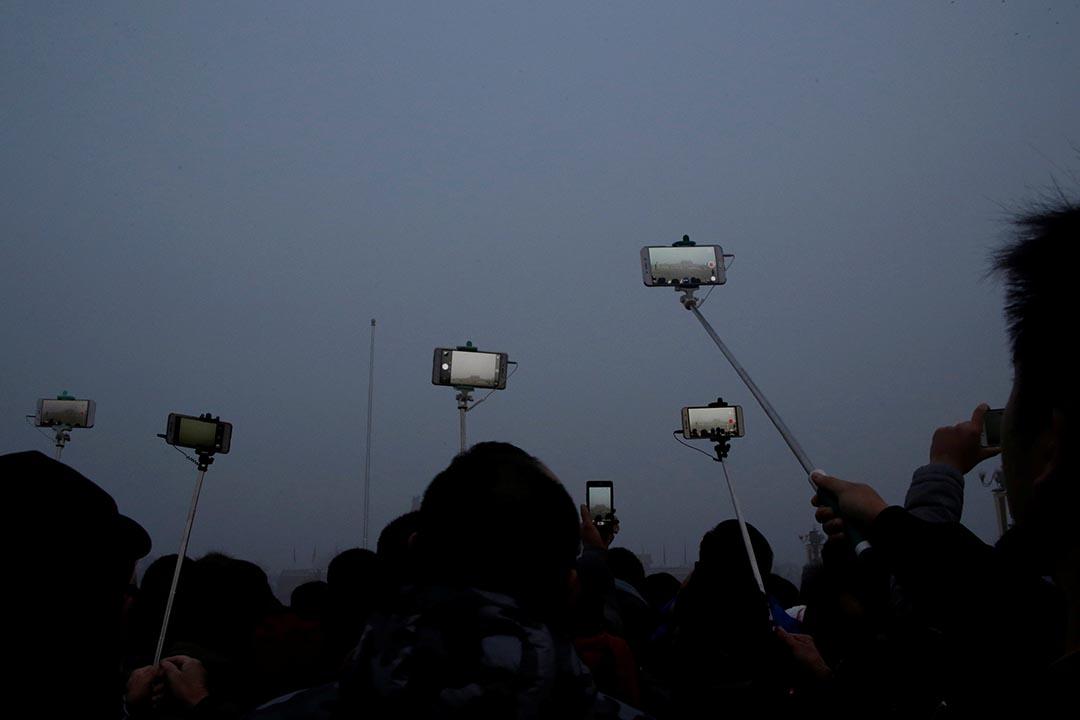中國北京,市民在霧霾中為天安門廣場的升𣄃儀式拍照留念。