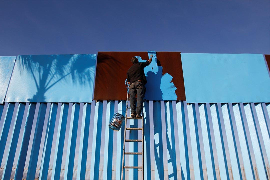 2016年12月10日,墨西哥蒂華納,一個藝術家在粉刷分隔墨西哥與美國的牆。