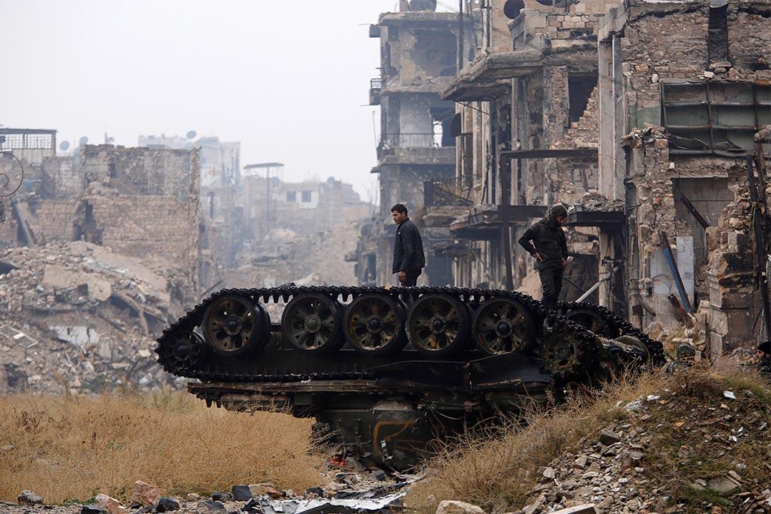 2016年12月13日,叙利亞阿勒頗,政府軍士兵站在一輛已毀壞的坦克上。