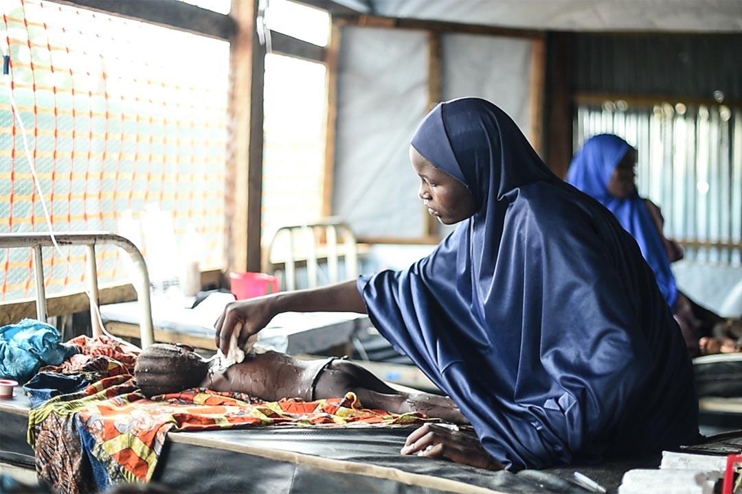 2016年8月,尼日利亞博諾州(Borno State, Nigeria),在丹博阿(Damboa)一間綜合醫院的隔離病房內,一個母親把沾濕了的毛巾放在女兒的身體上,希望幫助她退燒。她的女兒患上麻疹並出現併發症,正接受治療。病情最嚴重的個案會獲轉介至兩小時車程外、位於比烏(Biu)的醫院作進一步治療。