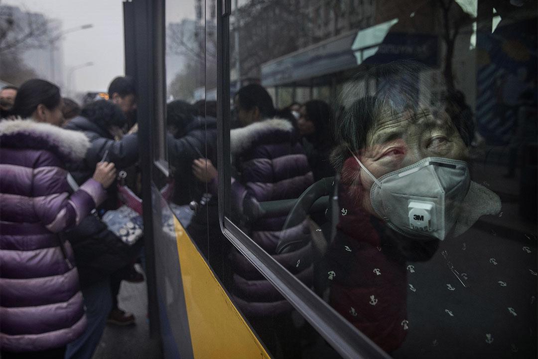2016年12月12日,中國北京,一個老人戴著口罩乘車。