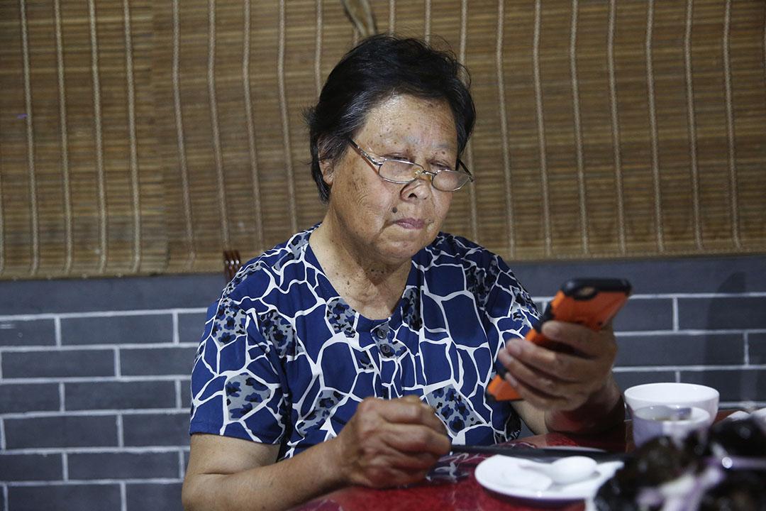 張煥枝在用手機查看網絡上關於聶樹斌案的最新報導。