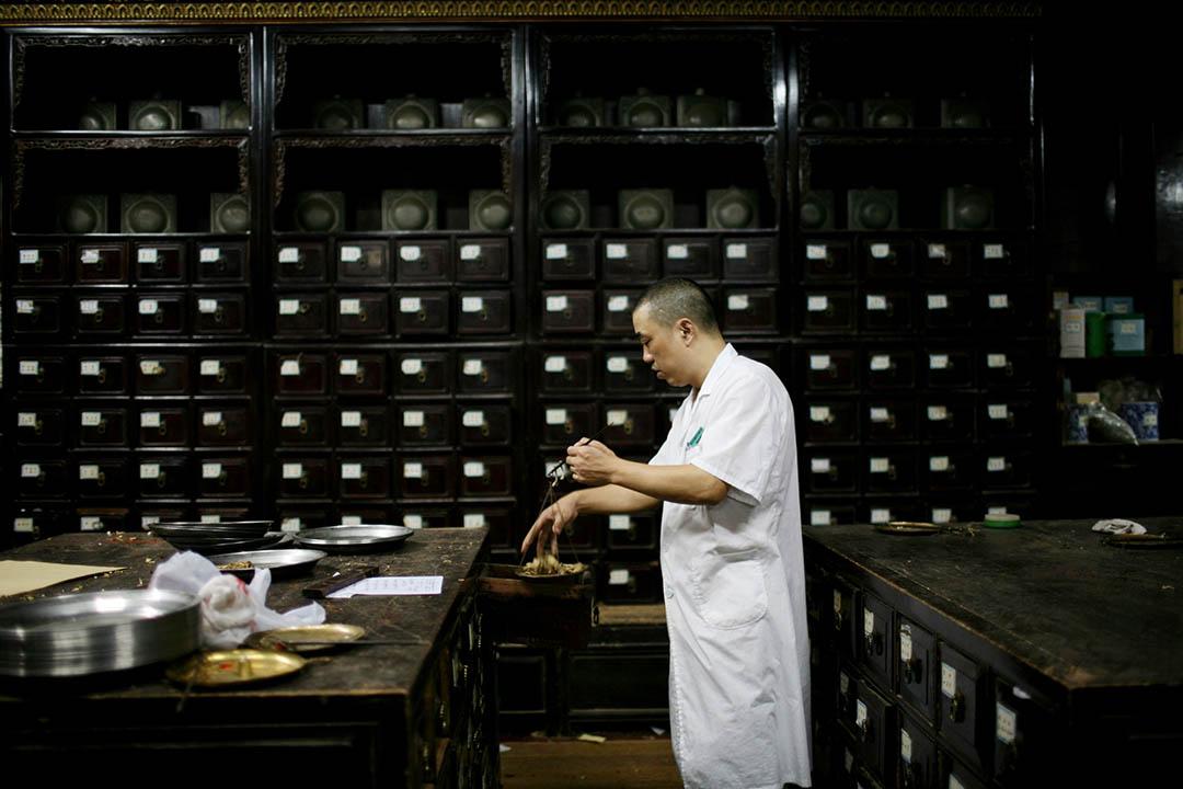 全國人大常委會通過中國中醫藥法。圖為中國浙江一家中醫藥店職員正在配藥。