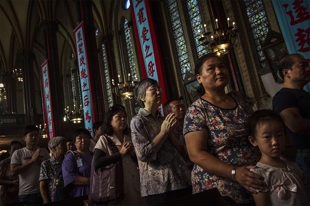 圖為2014年8月15日,北京天主教徒排隊輪候領取聖餐。