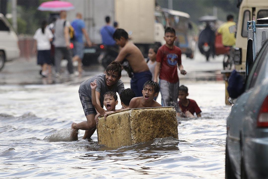 2016年12月8日,菲律賓馬尼拉低窪地區水浸,幾個男童用破冰箱作交通工具。