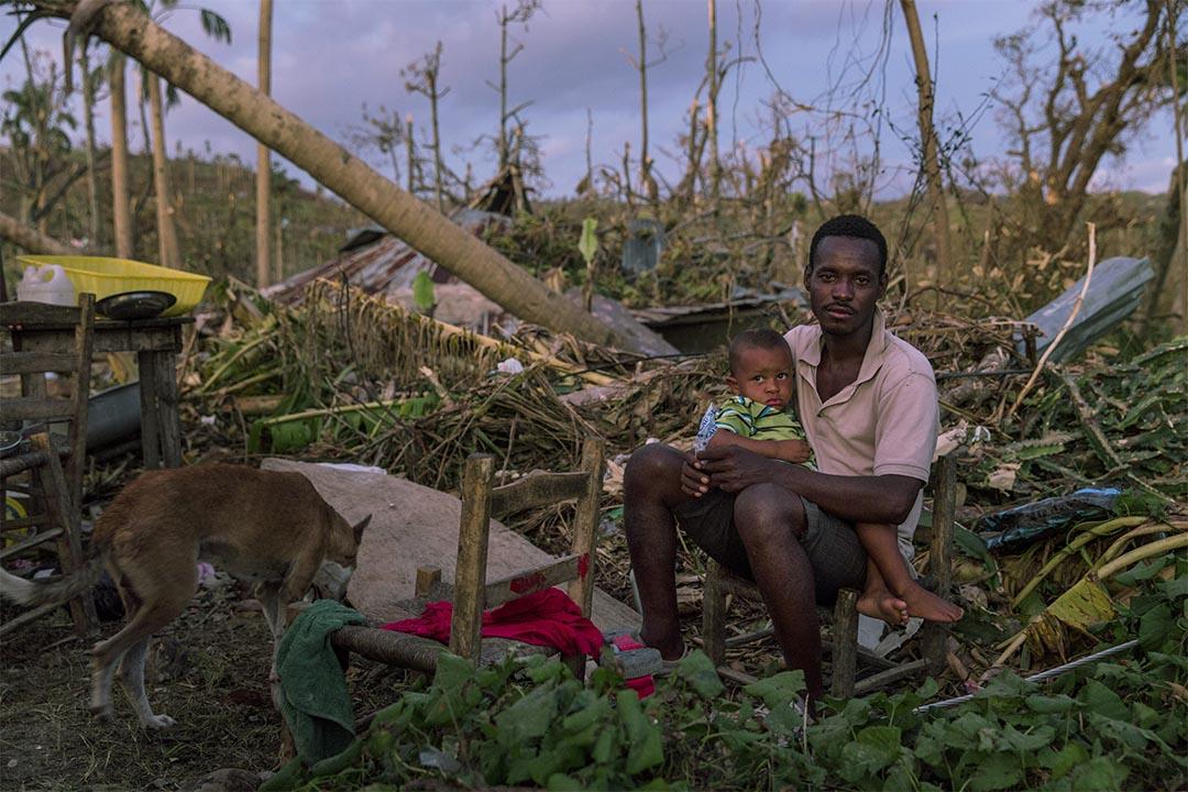 2016年10月,海地薩魯特港(Port Salut, Haiti),一名父親與兒子坐在被摧毀的家園上。颶風馬修在10月4日吹襲加勒比海,重創海地大部分地區。無國界醫生的團隊用盡所有交通,包括騎驢子,來運送醫療物資到山區中較遍遠的社區,這些社區大多被倒塌的大橋與道路所隔絕。
