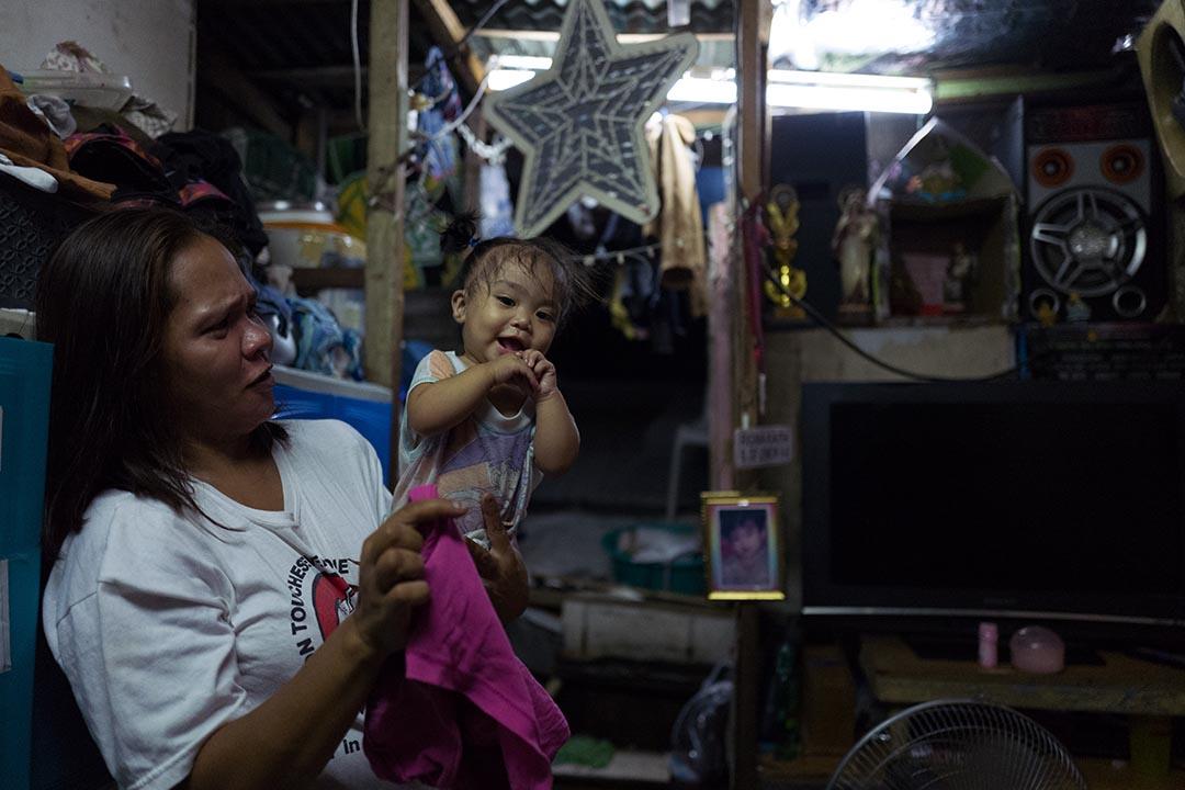 Gina De Lemon和她七個月大的幼女Rica。一家八口的家中,擺有一個小小的祭壇和聖母像。