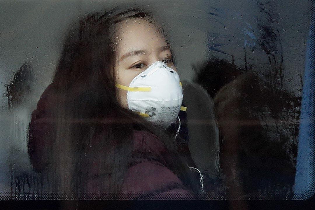 中國北京,一名女士帶著面罩乘坐巴士。