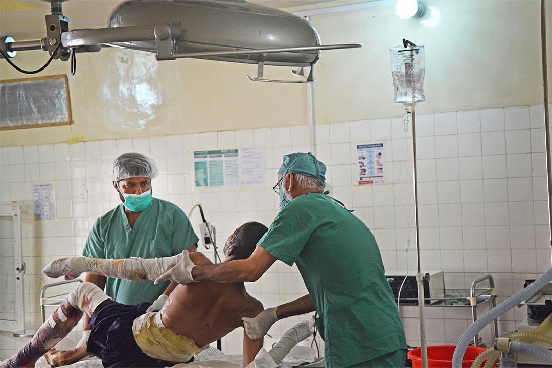 2016年5月,阿富汗拉什卡爾加(Lashkar Gah, Afghanistan),由無國界醫生支援的布斯醫院內,手術室人員把一個 20 歲男人移到手術床上準備作手術。該病人在巴士車禍中受傷,臉部和手臂嚴重燒傷。