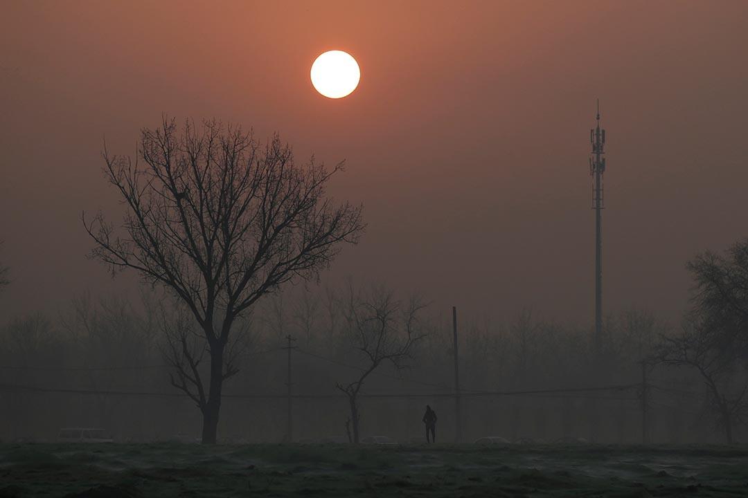 中國北京,一名市民在日出時份從霧霾中走過。