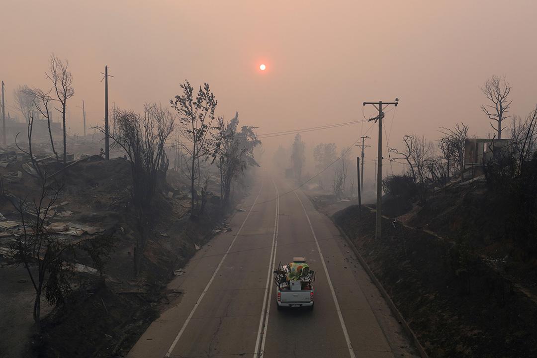 2017年1月26日,智利聖奧爾加,一輛裝滿傢私物品的汽車經過被山火焚燒的社區。這是智利中南部地區近代史上最嚴重的山火。