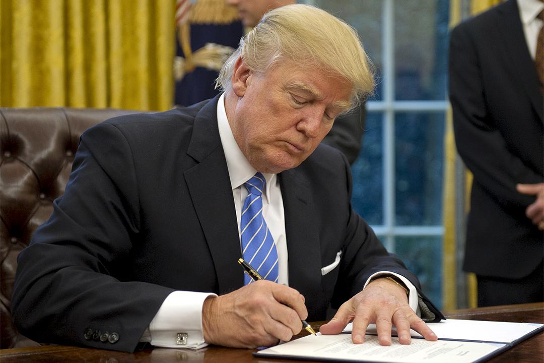 特朗普總統在2017年1月23日在華盛頓白宮橢圓形辦公室簽署三項行政命令。