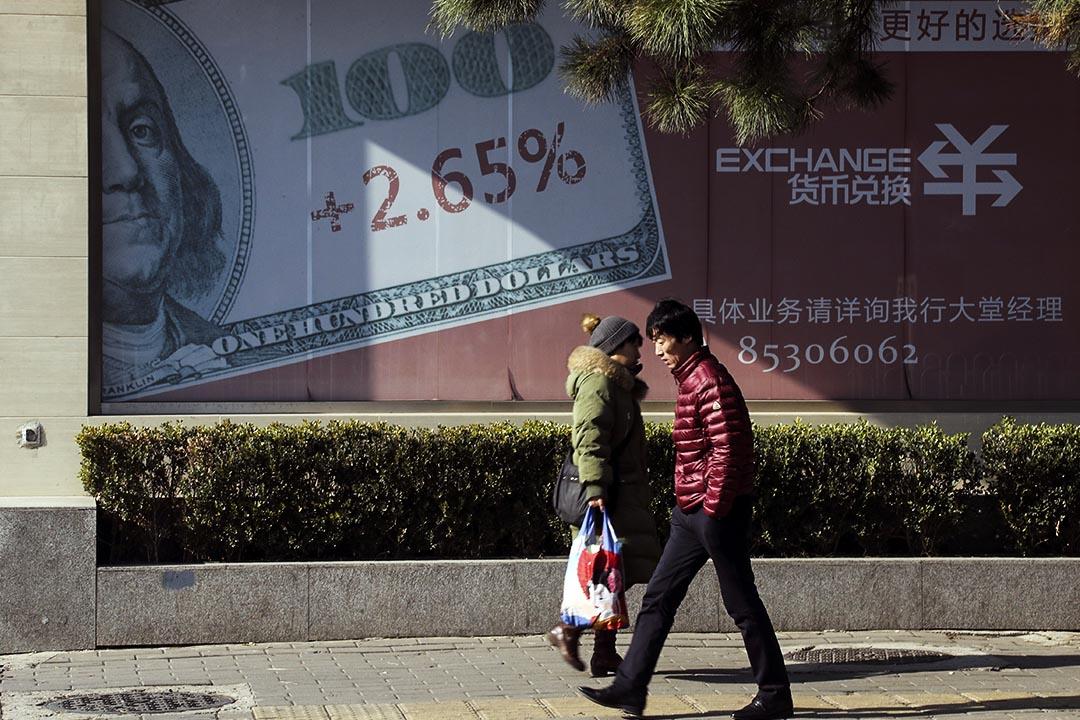 境內個人購匯監管加強,規定不得用於境外買房和證券投資。圖為2016年11月24日,北京,兩個人在一家銀行的廣告前走過。