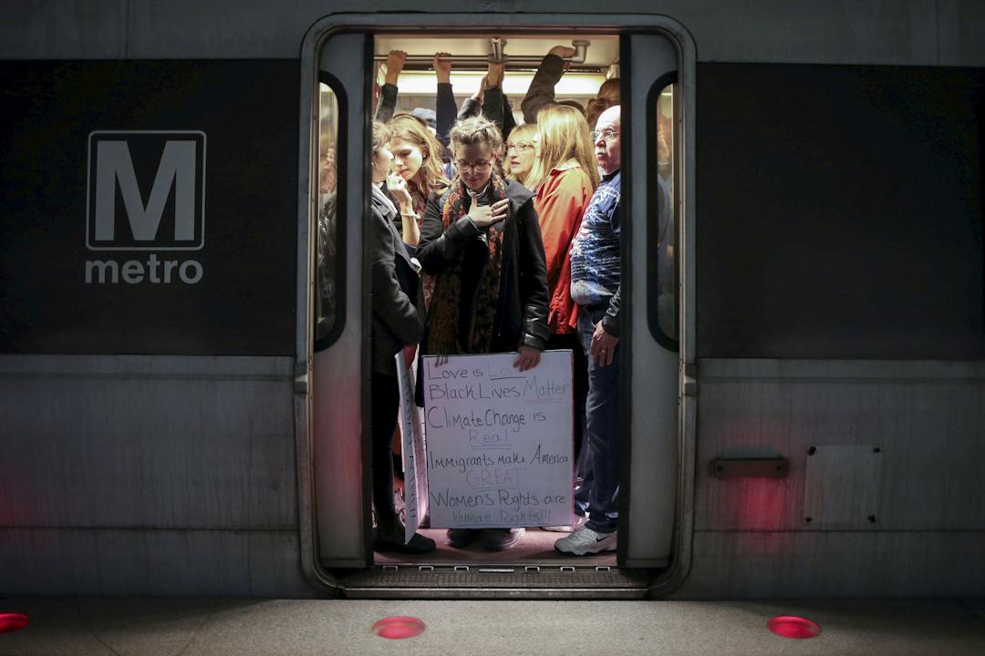 在美國華盛頓,拿着標語的女士正乘坐地鐵前往示威區。