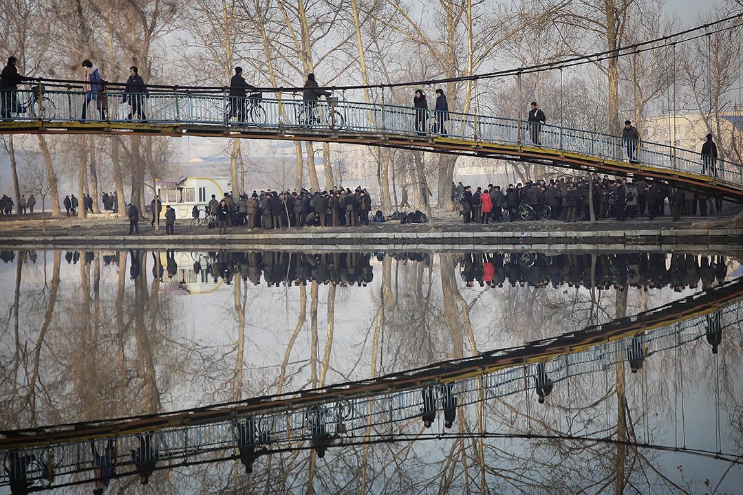 平壤,人們經過一座橋橫渡河流。