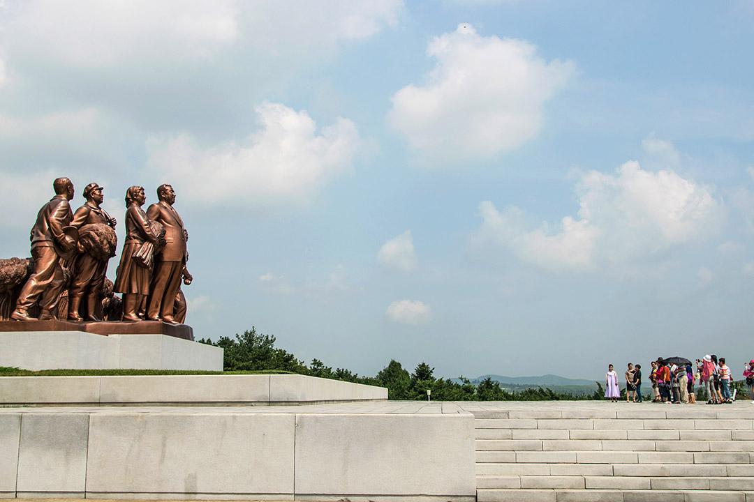 一班旅客在北韓平壤參觀金日成像。