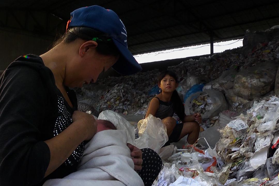 在廢舊塑料回收廠工作的母親,在廢品堆裏哺乳。